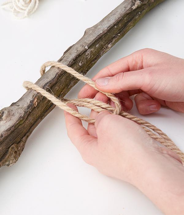 Den ersten Strang bindet man mit Hilfe einer Öse über den Holzstecken