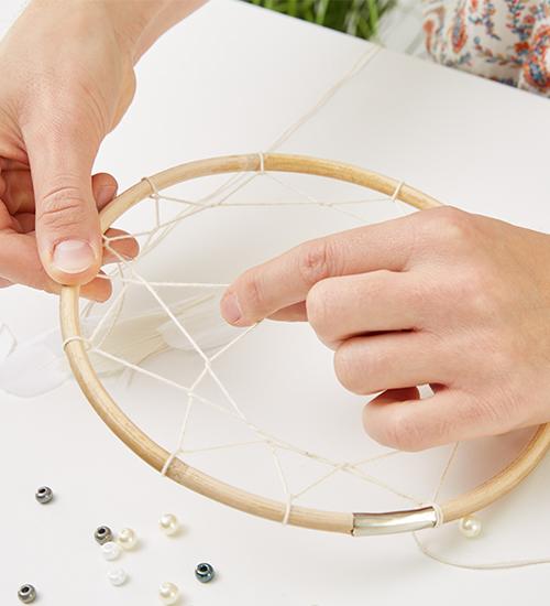 Das Netz des Traumfängers wird mit einem Garn geknüpft