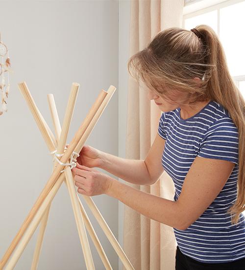 Die Rundhölzer passend platzieren und das Seil fest verknoten