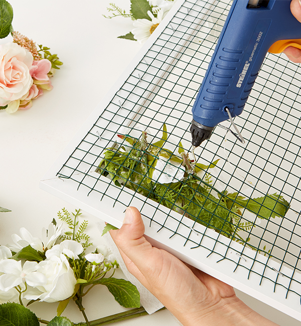 Kunstblumen mit dem Kleber und einem Stück Flies befestigen
