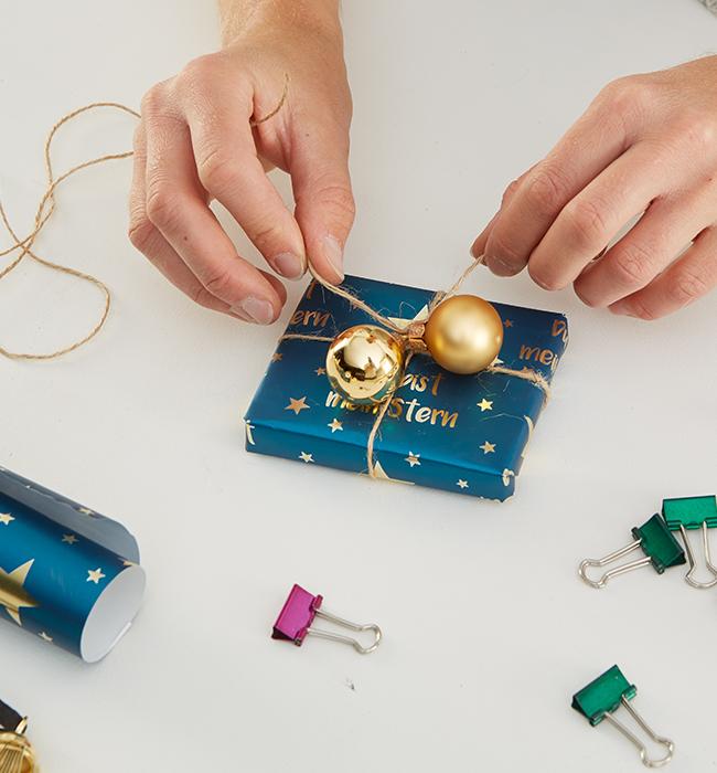 Süsses und Spielsachen in Geschenkpapier oder Geschenktüten packen