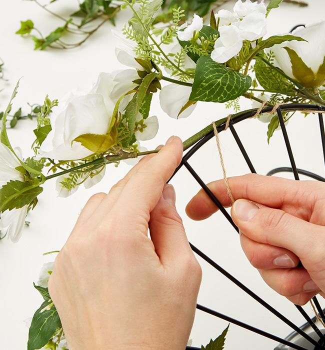 Zu Beginn bindet man die Kunstblumen um die Leuchte