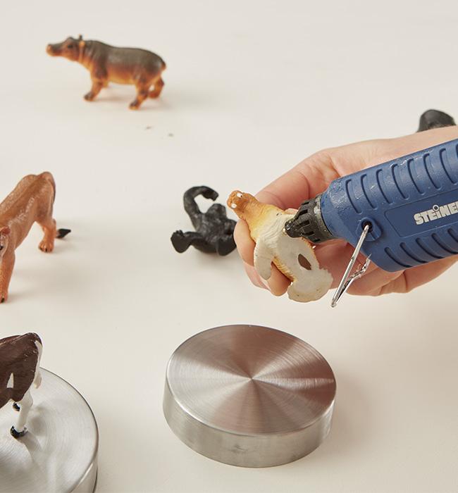 Plastikfiguren mit Hilfe einer Heißklebepistole befestigen
