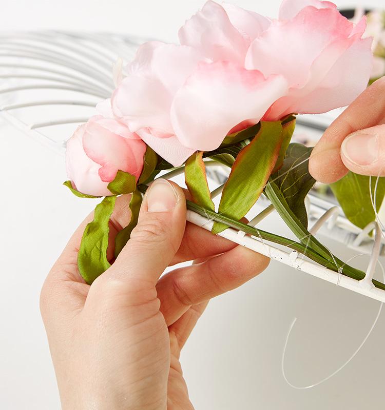 Kunstblumen mit Hilfe einer Angelschnur am Wandspiegel befestigen