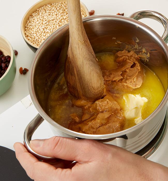 Butter, Erdnussbutter, Honig und Rohrzucker in einem Topf geben