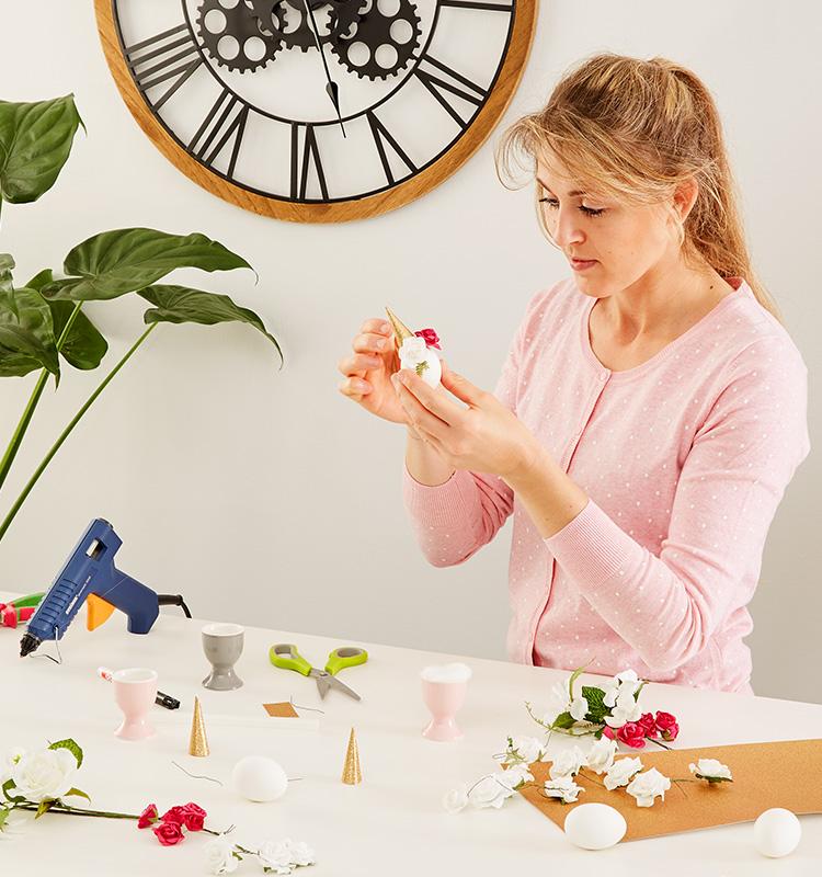 Horn und die Kunstblumen werden mittag auf das Ei geklebt