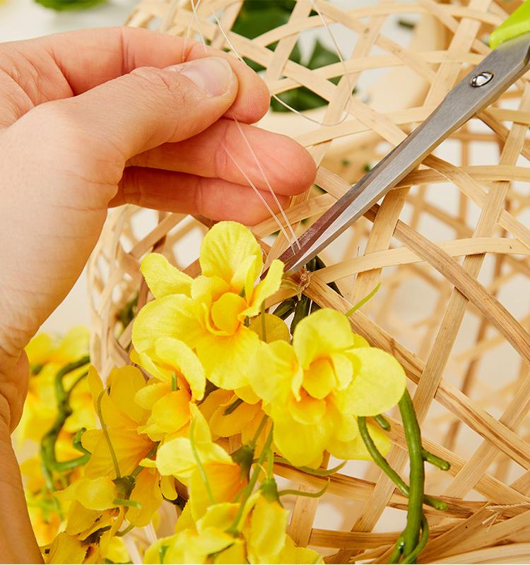 Kunstblumen mit Hilfe der Angelschnur am Geflecht der Laterne befestigen