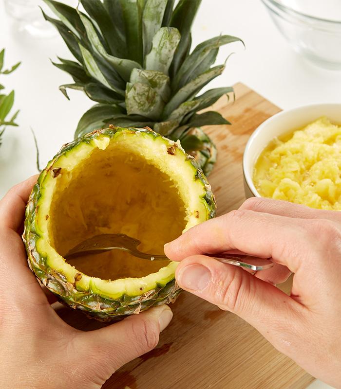 Ananas mit Hilfe eines Messers und Löffel aushöhlen