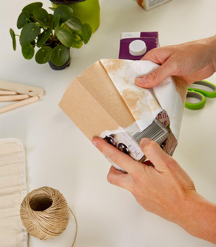 Die äußerste Papier-Plastikschicht vom Tetrapack abziehen