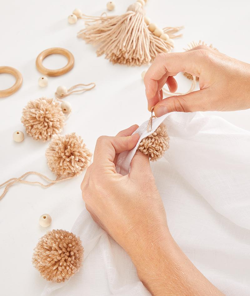 Pompons mit Zwirn und Nadel am Vorhang befestigen